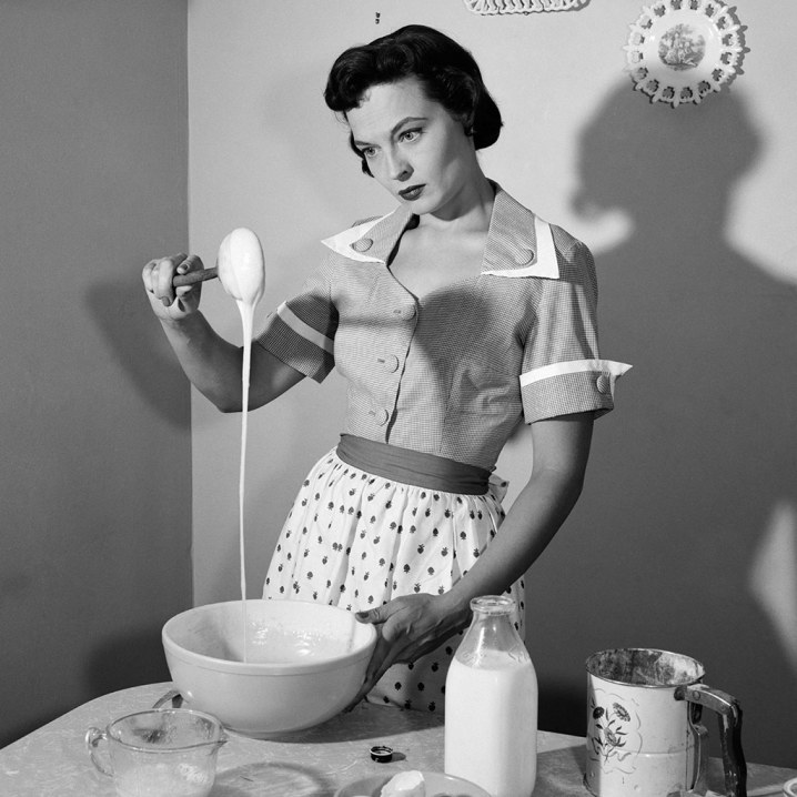 1960s Housewife Mixing Sticky Batter in Kitchen